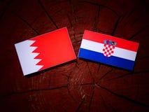 Флаг Бахрейна с хорватским флагом на изолированном пне дерева Стоковая Фотография