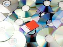 Флаг Бахрейна na górze кучи КОМПАКТНОГО ДИСКА и DVD на белизне Стоковые Фотографии RF