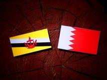 Флаг Брунея с бахрейнским флагом на пне дерева Стоковое Изображение