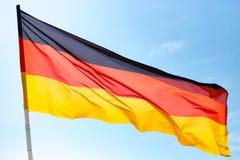 Флаг Германии против голубого неба Стоковые Фотографии RF