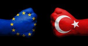 Флаг Европейского союза и Турции покрашенных на 2 сжатых кулаках Стоковое Фото