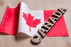Флаг Канады, слова Канады в деревянных абстрактных письмах, деревянной предпосылки Стоковое фото RF