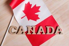 Флаг Канады, слова Канады в деревянных абстрактных письмах стоковые фото