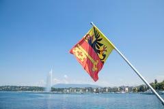 Флаг кантона Женевы в центре города Женевы, на озере Leman Иконическую струю воды Eau ` двигателя d можно увидеть Стоковая Фотография