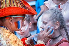 Флаг колумбийского болельщика рисуя русский на щеке молодого кавказского болельщика девушки на улице в центре Москвы Стоковая Фотография RF
