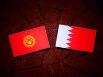 Флаг Кыргызстана с бахрейнским флагом на пне дерева Стоковое Фото