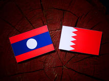 Флаг Лаоса с бахрейнским флагом на пне дерева Стоковое Изображение