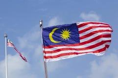 Флаг Малайзии также известный как волна Jalur Gemilang с голубым небом стоковое изображение