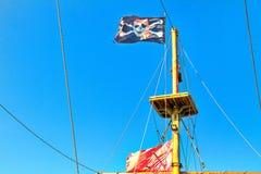 Флаг пирата поднятый против голубого неба стоковые изображения rf