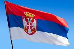 Флаг республики Сербии против голубого неба Стоковая Фотография