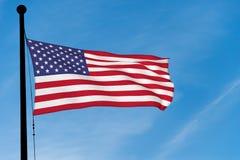 Флаг США развевая над голубым небом стоковые изображения