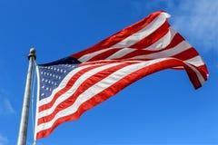 Флаг США развевая против ясного голубого неба на яркий солнечный день Стоковые Изображения RF