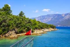 Флаг Турции на смычке корабля на фоне живописного берега и гор моря Стоковое Изображение RF