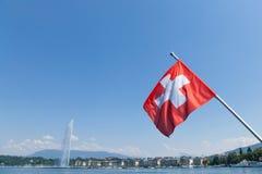 Флаг флага Switerland в центре города Женевы, на озере Leman Иконическую струю воды Eau ` двигателя d можно увидеть Стоковые Изображения