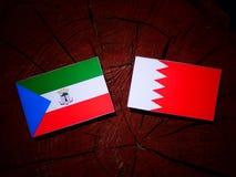 Флаг Экваториальной Гвинеи с бахрейнским флагом на isolat пня дерева Стоковые Изображения