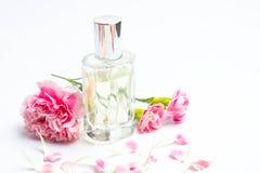 Флаконы духов и розовые гвоздики на белой предпосылке Стоковые Фотографии RF
