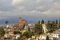 Фланк холма района Albayzin, Гранады, с римской церковью на верхней части и белыми традиционными домами на наклонах на пасмурный  стоковое изображение