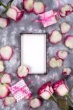 Флористическая рамка: букет розовых белых роз и подарочных коробок на каменной предпосылке с космосом экземпляра для текста Стоковые Фото