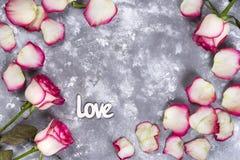 Флористическая рамка: букет розовых белых роз и подарочных коробок на каменной предпосылке с космосом экземпляра для текста Стоковое Фото
