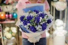 Флорист держа нежный состав цветка в голубых тонах состоя из мягких и красивых цветков Стоковое Изображение