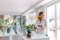 Флорист женщины работая в цветочном магазине Стоковые Изображения RF