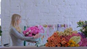 Флорист оборачивает цветки в бумаге подарка на цветочном магазине видеоматериал