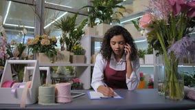 Флорист принимая заказ по телефону в цветочном магазине видеоматериал