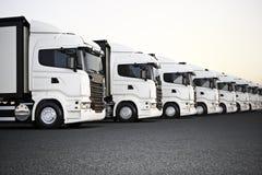Флот белых коммерчески тележек транспорта припарковал в ряд готовое для распределения дела Стоковое Изображение RF