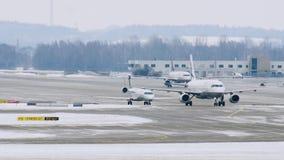 Флот самолетов двигая дальше взлётно-посадочная дорожка, авиапорт Мюнхена, Германию