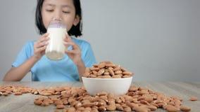 Фокус молока миндалины азиатской маленькой девочки выпивая отборный на молоке сток-видео
