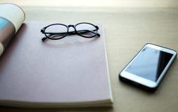 Фокус на стеклах с сотовым телефоном и книгой Стоковое Изображение RF