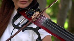 Красивая маленькая девочка играя на электрической скрипке на красивом парке сток-видео