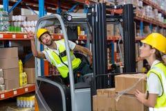 Фокус работника сидя на тележке паллета указывает полки Стоковое фото RF