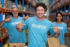 Фокус счастливого волонтера показывая его футболку перед его командой Стоковое фото RF