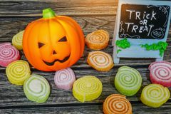 Фокус украшения хеллоуина или обслуживание, тыква Джек-o-фонарика с конфетой на деревянной предпосылке Стоковые Изображения RF