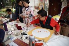 Фольклорный мастер который делает китайские вентиляторы стоковая фотография