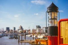 Фонарик красного света в HafenCity ght Перенесите пристани с кораблями и яхтой на анкер в предпосылке Германия hamburg стоковое изображение