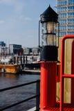Фонарик красного света в HafenCity ght Перенесите пристани с кораблями и яхтой на анкер в предпосылке Германия hamburg стоковые изображения