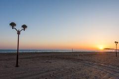 Фонарик стоит на побережье и в темноте освещает пляж стоковое изображение