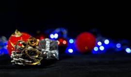 Фоновое изображение рождества, красные шарики на запачканной предпосылке, голубые света, фокус на конусе сосны стоковая фотография
