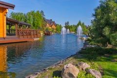 Фонтаны на искусственном озере около деревянных домов Большое место, который нужно ослабить на открытом воздухе Стоковые Фото