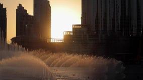 Фонтаны петь на заходе солнца вечера около Burj Khalifa сток-видео