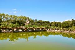 Фонтан в саде окруженном прудом Стоковое Изображение