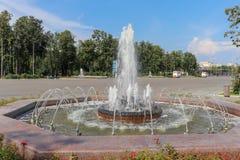 Фонтан города в парке Красные цветки рядом с фонтаном стоковые изображения