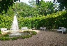 Фонтан и белые benchs сада в тихом зеленом парке Стоковое Изображение