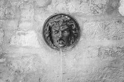 Фонтан улицы с головой Медузы в предпосылке кирпичной стены Стоковые Изображения