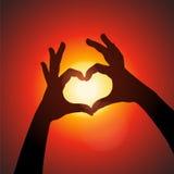 Форма влюбленности вручает силуэт в небе Стоковые Изображения RF