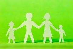 Бумажная семья на зеленой предпосылке Стоковые Изображения RF