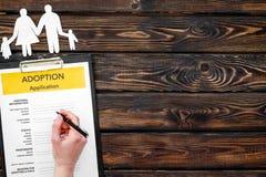 Форма для заявления для принимает ребенка на деревянной насмешке взгляда сверху предпосылки вверх стоковое изображение rf