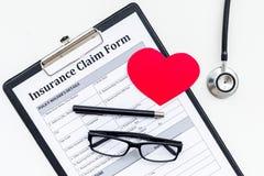 Форма заявки медицинской страховки для заполняет вне Пустая форма около знака сердца и стетоскоп на белом взгляд сверху предпосыл стоковая фотография rf